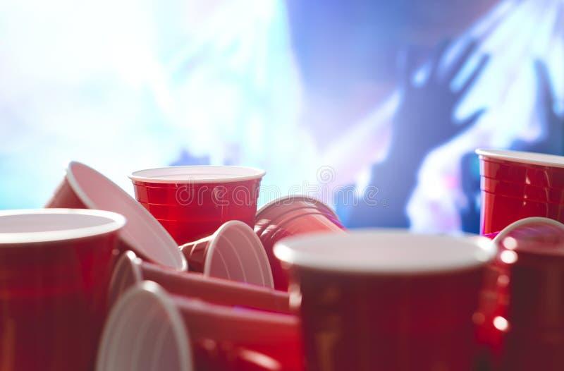 Beaucoup de tasses rouges de partie avec les personnes de célébration brouillées à l'arrière-plan Récipients d'alcool d'universit photo libre de droits