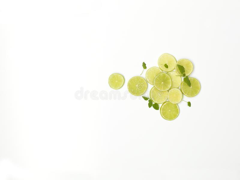 Beaucoup de tranches fraîches de chaux avec la menthe sont admirablement arrangées sur un fond blanc photo libre de droits