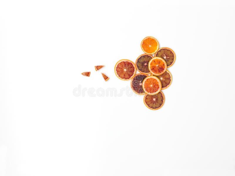 Beaucoup de tranches fraîches d'oranges sanguines se trouvent admirablement disposé sur un fond blanc image stock
