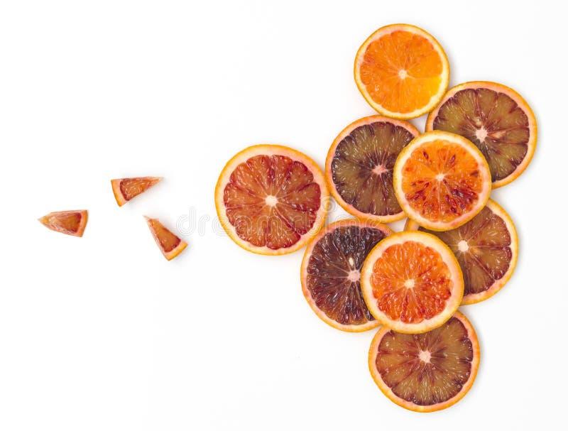 Beaucoup de tranches fraîches d'oranges sanguines se trouvent admirablement disposé sur un fond blanc photographie stock libre de droits