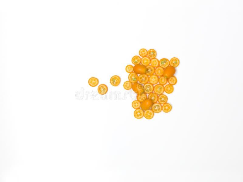 Beaucoup de tranches fraîches de kumquat se trouvent admirablement disposé sur un fond blanc images stock