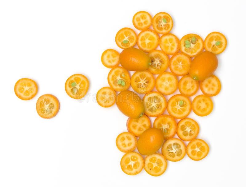 Beaucoup de tranches fraîches de kumquat se trouvent admirablement disposé sur un fond blanc photos stock