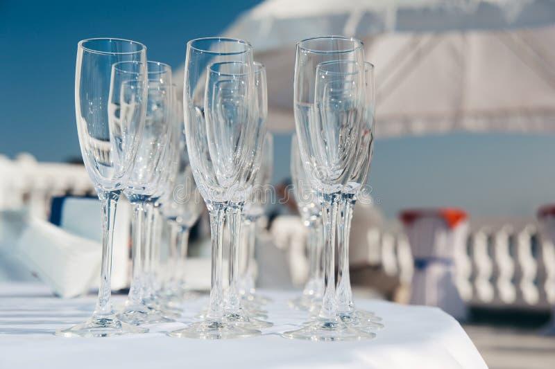 Beaucoup de verres à vin vides dans les rangées à la table blanche Verre de bienvenue restauration photographie stock libre de droits