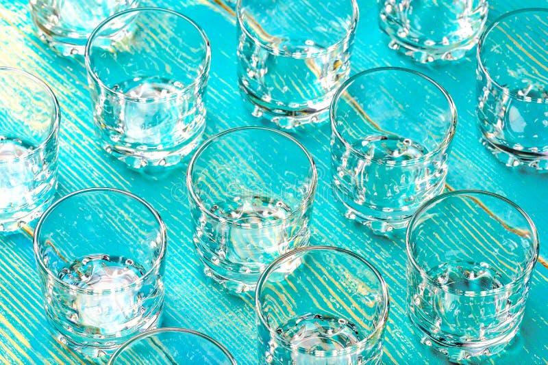 Beaucoup de verres vides pour la vodka sur une table bleue de bois photo stock