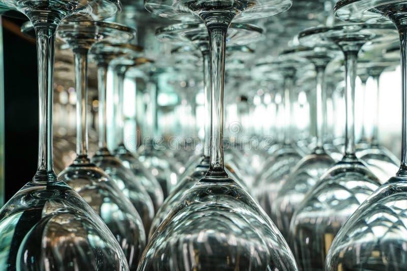 Beaucoup de verres de vin à l'envers pendant d'une rangée photos stock
