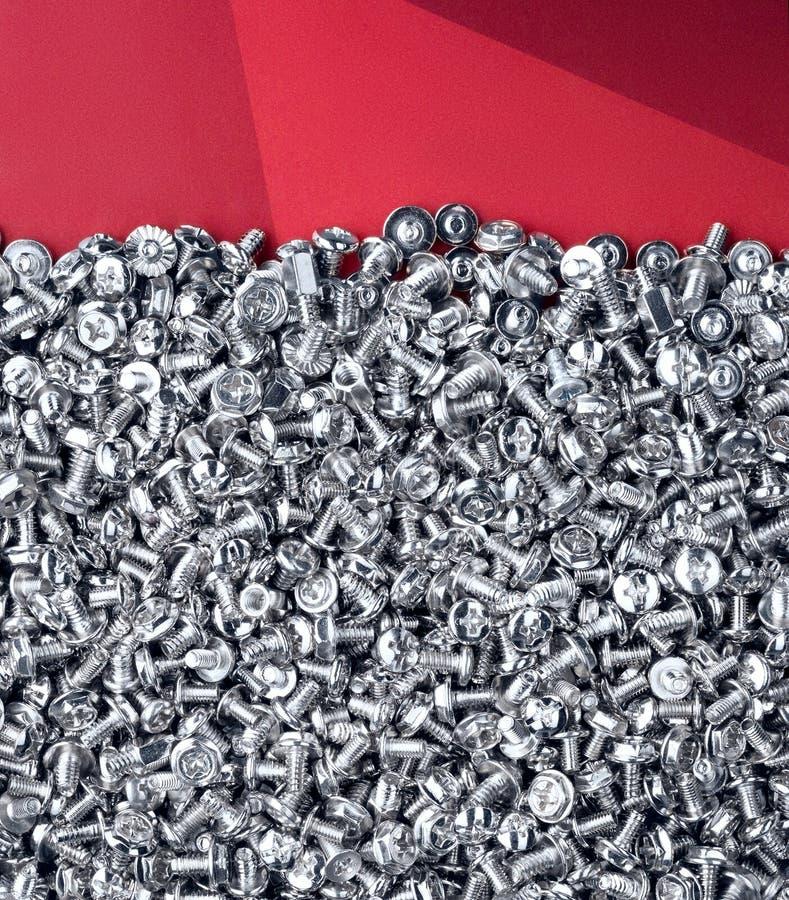 Beaucoup de vis en acier d'ordinateur Fond rouge photo stock