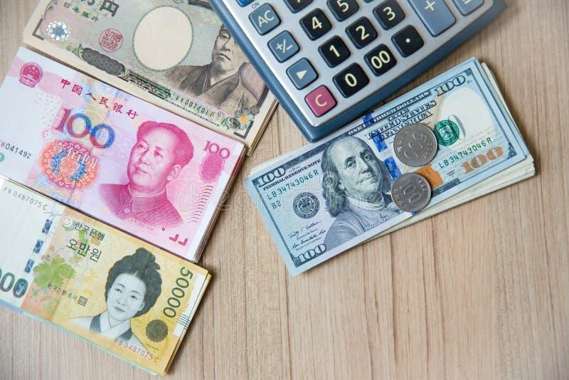 Beaucoup devise de billet de banque, Yen-Japon, euro-UE, yuan-Chine, gagner-Corée avec la calculatrice et les pièces de monnaie I images stock