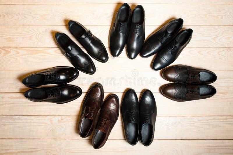 Beaucoup garnissent en cuir les chaussures des hommes sur le fond en bois photographie stock libre de droits