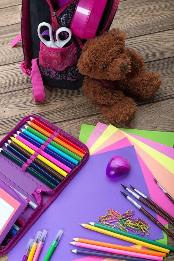 Beaucoup instruisent la papeterie, sacs d'école, ours de nounours, un tas photo stock