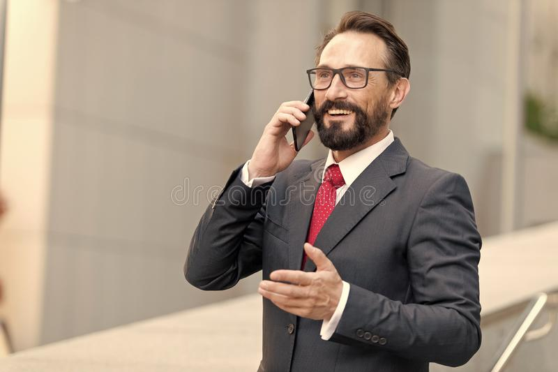 Beaucoup ! L'homme d'affaires barbu parle par le téléphone et rit Vue d'un jeune homme attirant d'affaires en verres utilisant le images stock
