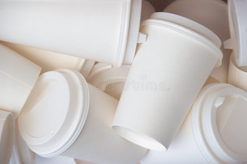Beaucoup masquent pour emporter le fond blanc de tasses de café faux  photo libre de droits
