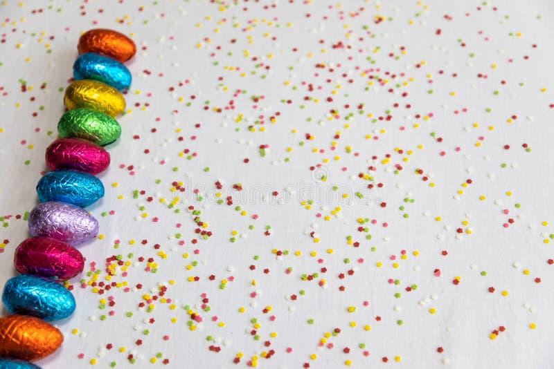Beaucoup ont align? les oeufs de p?ques color?s de chocolat sur le fond blanc et les confettis color?s photo stock