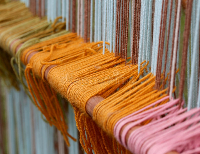 Beaucoup rangée de thèse colorée de laine dans le vieux métier à tisser de tissage de textiles image libre de droits