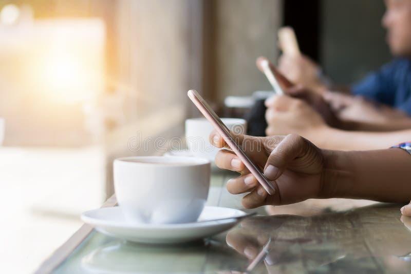 Beaucoup remettent utilisant le smartphone dans le café photo stock