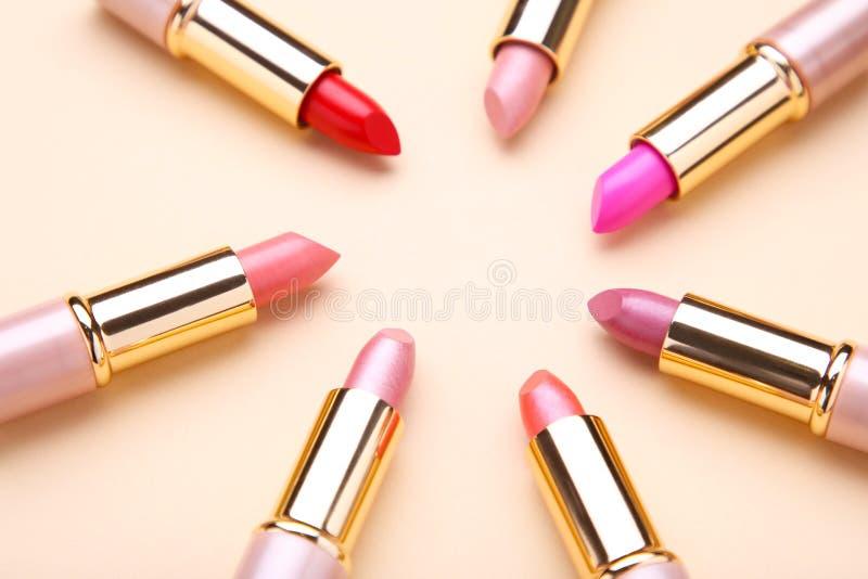 Beaucoup rouge à lèvres coloré sur le fond beige, configuration plate photo libre de droits