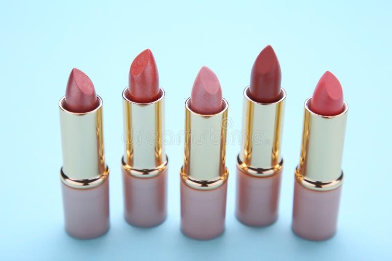 Beaucoup rouge à lèvres coloré sur le fond bleu, fin  photos libres de droits