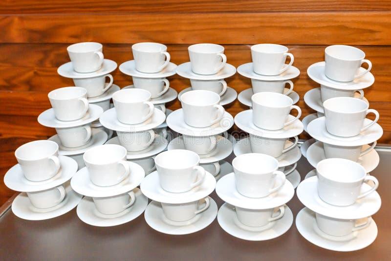 Beaucoup vident les tasses blanches de thé ou de café empilées sur le Tableau Service de approvisionnement d'événement images stock