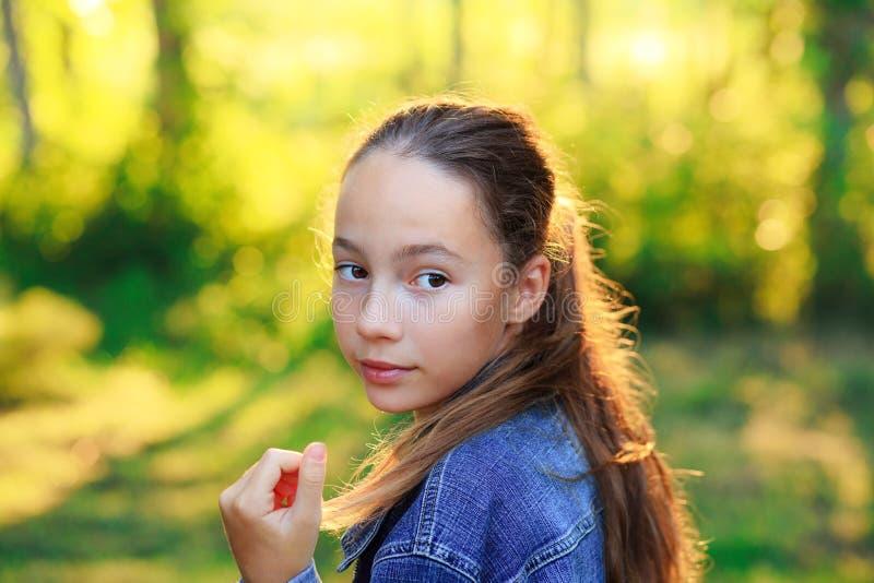 Beauece Teen Girl kijkt naar de camera en glimlacht in het park in de zonsondergang stock afbeeldingen