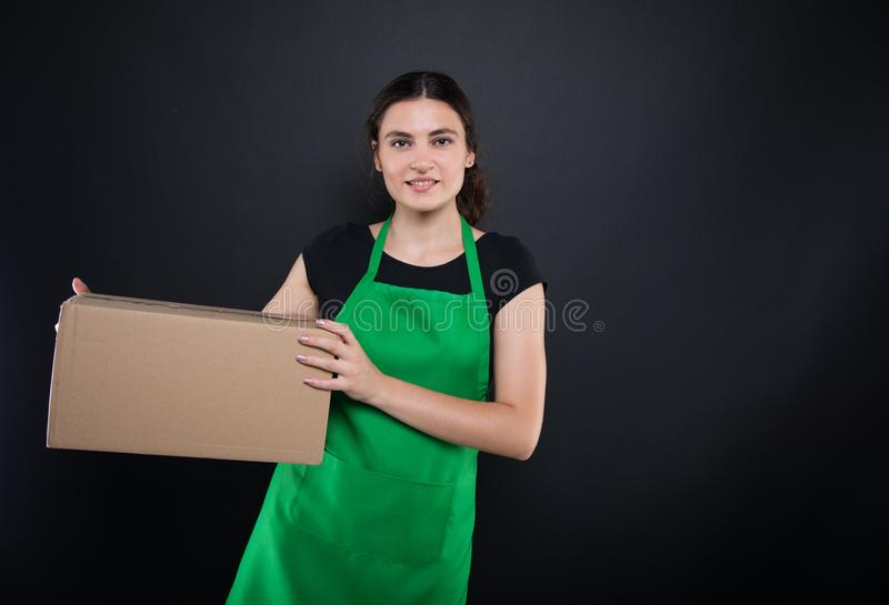Beauiful girl clerk holding a big box. In her arms for the store on dark background stock image