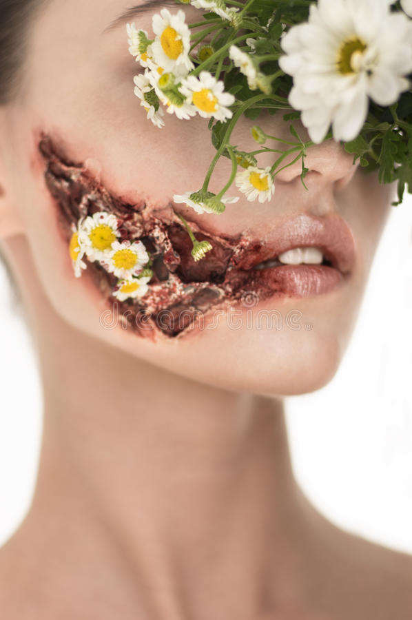 Beauiful girl with huge wound. On cheek and flowers covering face royalty free stock image
