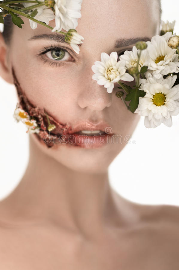 Beauiful girl with huge wound on cheek and flowers covering face. In studio royalty free stock photography
