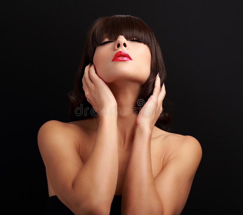 Beauiful female model with short hairstyle posing touching the hands hair. With closed eyes and red lipstick stock images
