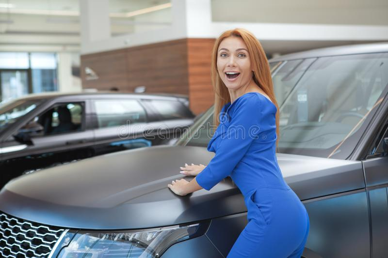Gorgeous woman choosing a new car at the dealership. Beauitful excited woman screaming happily, celebrating buying new car. Attractive female driver looking royalty free stock image