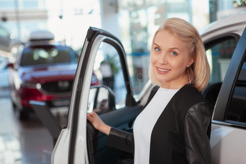 Beauitful woman buying new car at the dealership stock photo