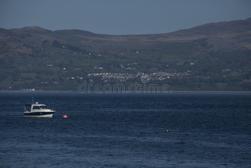 Beaumaris, Noord-Wales - blauwe wateren en een boot stock afbeelding