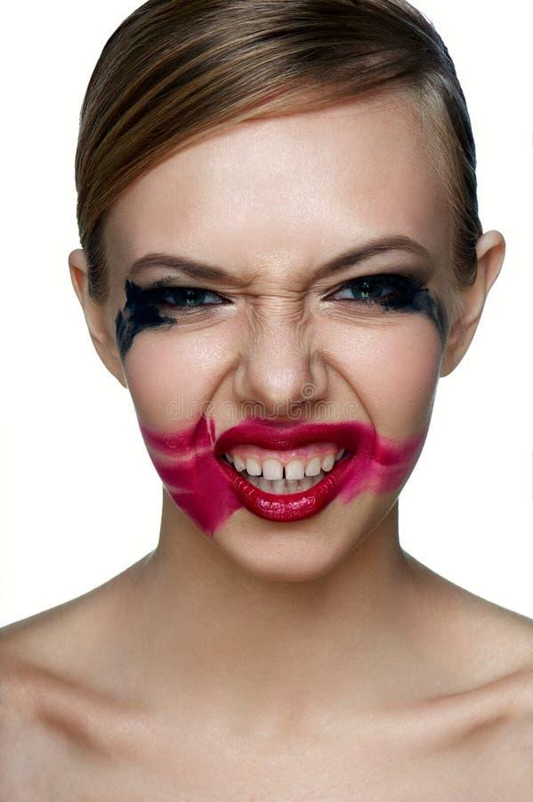 Beaury kwaad Meisje met enge Glimlach Gesmeerde Mascara en Lippenstift stock foto
