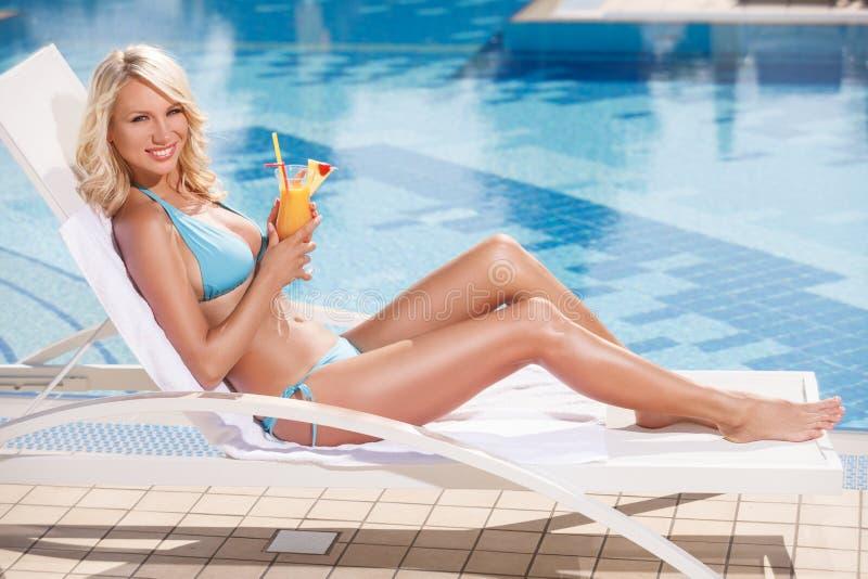 Beauté avec le cocktail. Jeunes femmes attirantes dans le bikini se trouvant dessus photographie stock