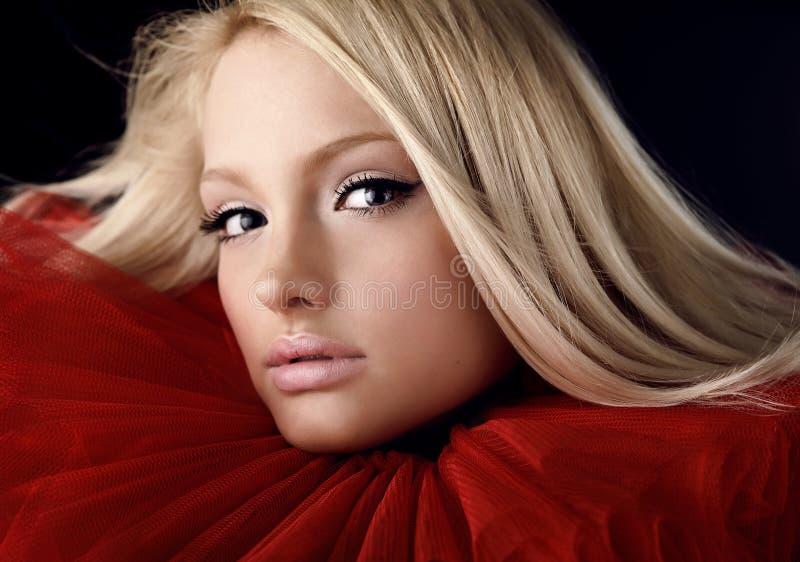 Beauté blonde attrayante dans le jabot théâtral rouge images stock