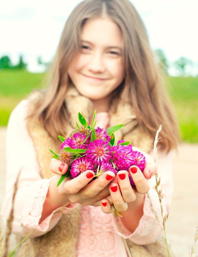 Beauté de nature Jeune fille de sourire tenant le flowe de trèfle de pré image libre de droits