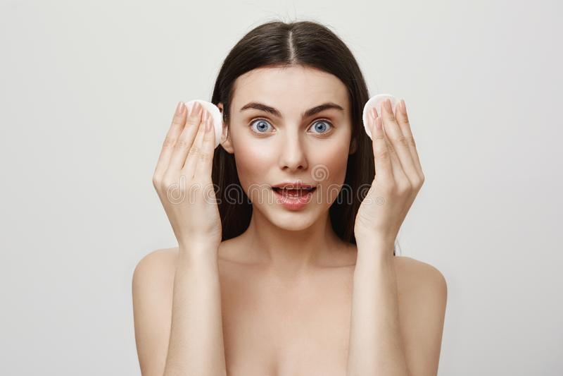 Beauté et concept cosmetological de procédure Portrait de la femme expressive belle tenant des protections de coton dans des main photo libre de droits