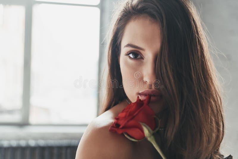 Beauté magnifique Jeune femme attirante tenant une rose et un l rouges photographie stock libre de droits