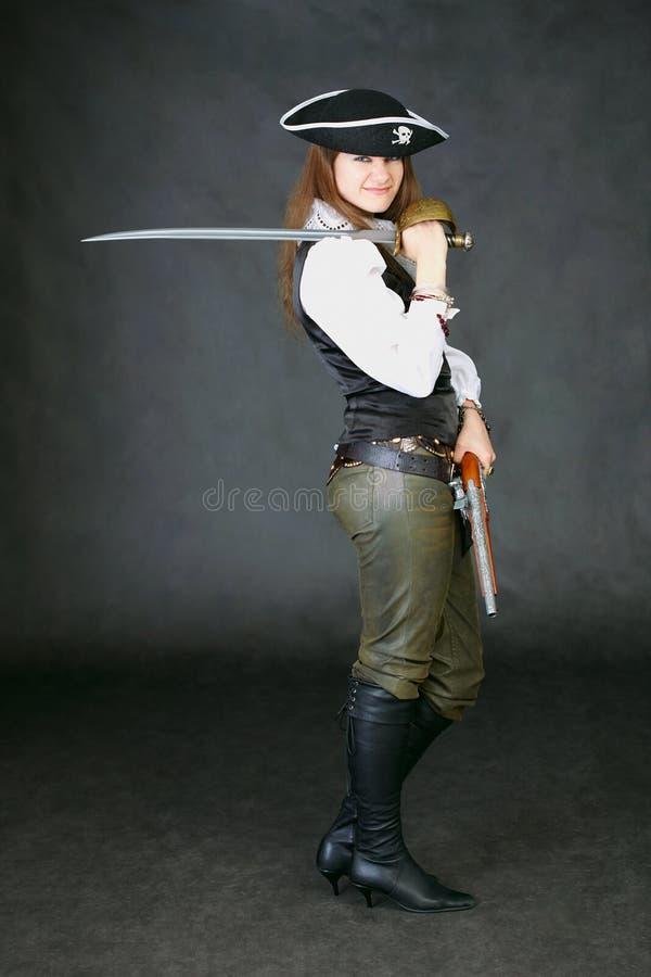 Beauté rectifiée comme pirate sur le noir avec l'épée image libre de droits