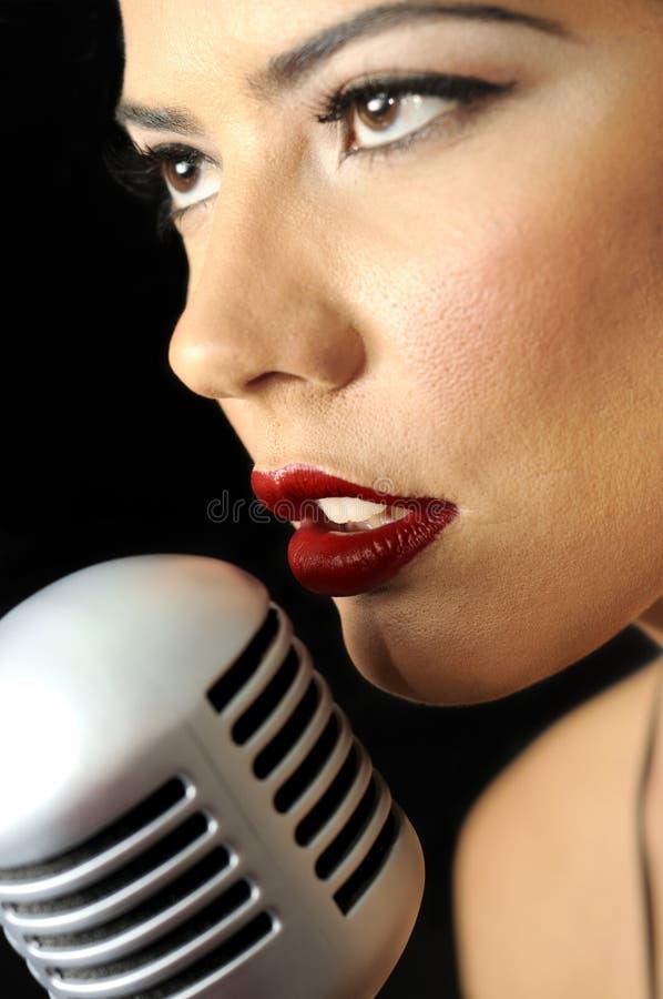 Beauté rouge de languettes chantant avec la rétro MIC images stock