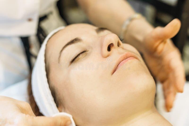 Beauté, station thermale et concept de cosmétologie La jeune fille se trouve avec les yeux fermés, docteur de cosmetologist faisa photos stock