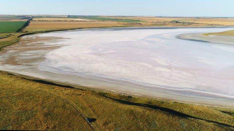 Beauté stupéfiante du lac salé sec de couleur beige légère entouré par les champs verts et jaunes projectile Vue a?rienne de photos stock