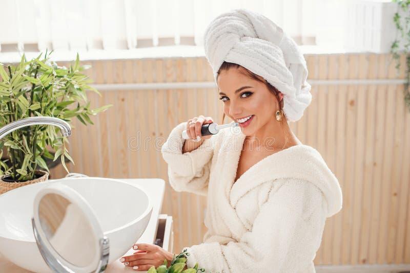 Beaut? et concept de soins de sant? La jeune femme de sourire attirante dans le peignoir tient une brosse ? dents dans la main et photos libres de droits