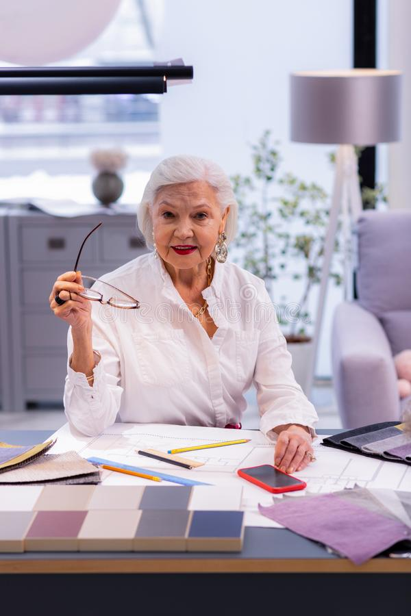 Beauteous aging executive comely sitting at deluged with papers table. Working elderly lady. Beauteous aging executive wearing cotton shirt with nice short royalty free stock photography