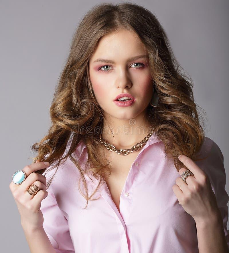 Beauteous Kasztanowa kobieta Trzyma Jej Hairs w Lekkiej bluzce zdjęcie stock