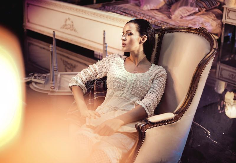 Beautfiul young lady resting in a luxurious, antique armchair royalty free stock images