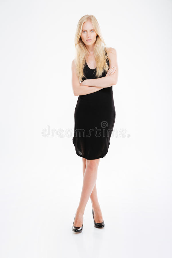 Beautful-Frau im schwarzen Kleid, das mit den Armen gefaltet steht lizenzfreie stockfotos