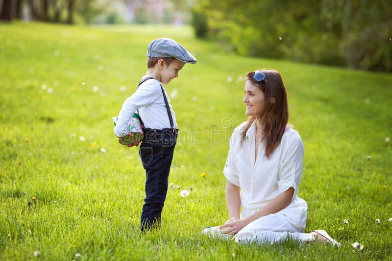 Beautful kid and mom in spring park, flower and present. Mothers day celebration concept stock photography