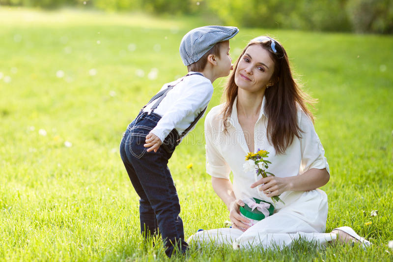 Beautful kid and mom in spring park, flower and present. Mothers day celebration concept royalty free stock images