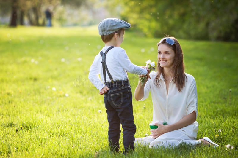 Beautful kid and mom in spring park, flower and present. Mothers. Day celebration concept stock photo