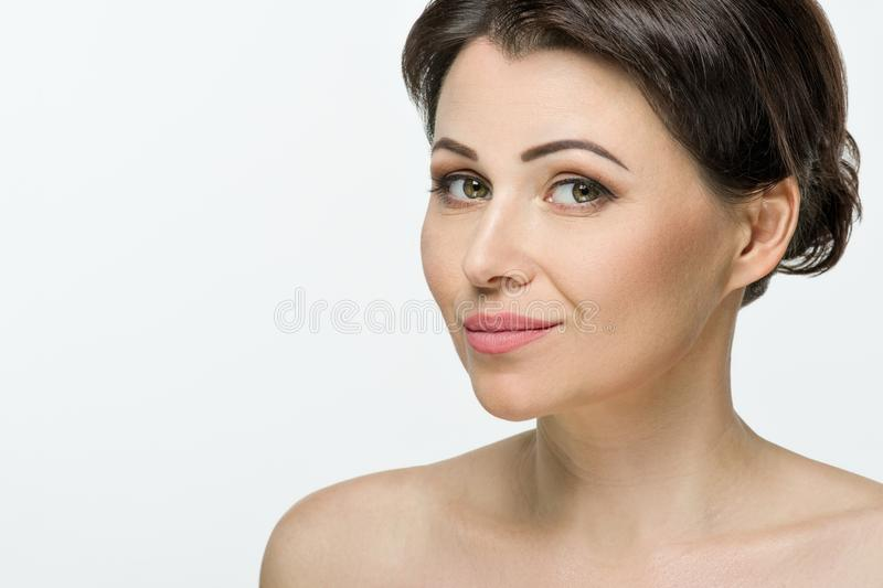 Beauti portrait of adult woman, white studio background, copy space royalty free stock images