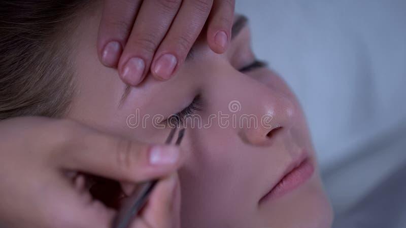 Beautician επέκτασης Eyelash που προσθέτει τον όγκο στα μαστίγια της γυναίκας, σαλόνι ομορφιάς στοκ φωτογραφίες με δικαίωμα ελεύθερης χρήσης