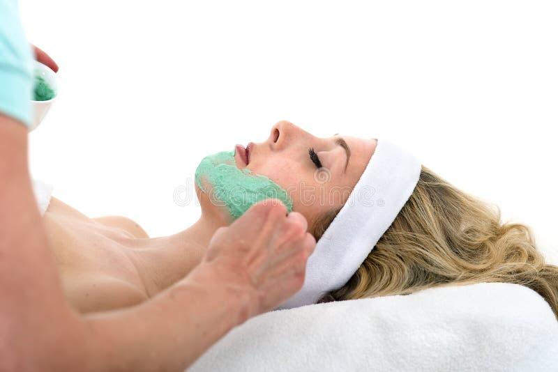 Beautician που εφαρμόζει την του προσώπου μάσκα στην όμορφη γυναίκα. στοκ φωτογραφία